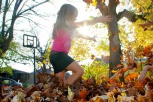 落ち葉で遊ぶ子供
